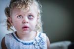 Sad and Frightened Little Girl with Bloodshot and Bruised Eyes.
