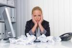 Eine Frau im Büro mit Papierknäuel. Ärger, Stress und Frust am Arbeitsplatz